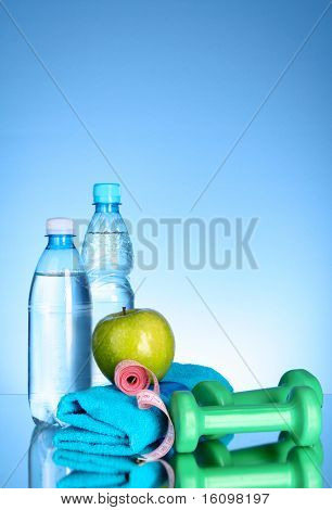Blue bottle of water, apple, sports towel,dumbbells and measure tape on blue background