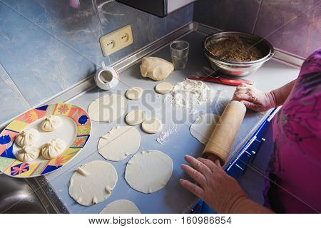 Grandmother roll dough. Senior woman hands rolling out dough in flour with rolling pin in her home kitchen.