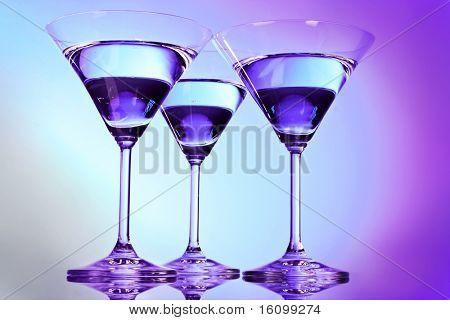 Tres vasos de martini sobre fondo púrpura