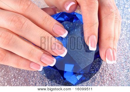 Beautiful woman hands with french manicure on blue background