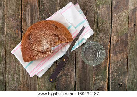 Rye bread and glass of water. On a pure towel bread and a knife nearby a glass of water lies. products on an old wooden table rural style