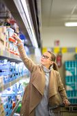 Beautiful young woman shopping for groceries and fruits and vegetables in produce department as well poster