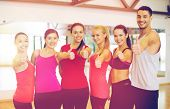 fitness, sport, training, gym and lifestyle concept - group of happy people in the gym showing thumb poster