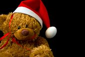 stock photo of teddy-bear  - Close up Teddy bear with Christmas hat looking at camera on black background - JPG
