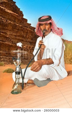 Bedouin with nargiila in the desert, Wadi Rum, Jordan