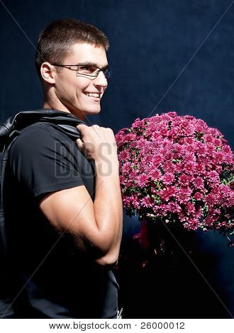Romantic man with glasses holding big bouquet of flowers to woman for Valentine's Day.
