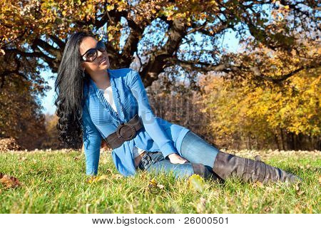 Happy beautiful woman with sunglasses sitting in the autumn park