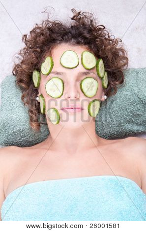 Woman relaxing under a cucumber face masque on her face