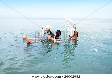 MADABA - SEPTEMBER 22: People shown with mud masks, float in the Dead Sea while reading on Septemter 22. 2010 in Madaba, Jordan.