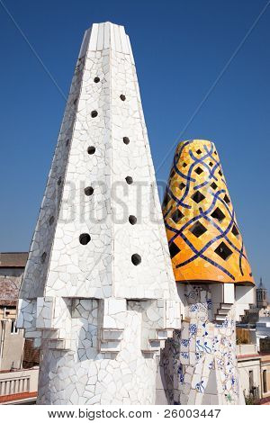 BARCELONA, SPAIN - OCTOBER 2:The mosaic chimneys made of broken ceramic tiles on roof of Palau Güell , one of the earlest Gaudi's  masterpieces  on October 02, 2011 in Barcelona, Spain