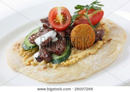 Pita topped with hummus and lamb