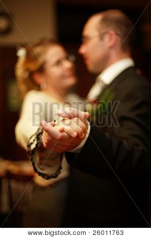 Just married bride and bridegroom are dancing, shallow DOF, sharped on the hands