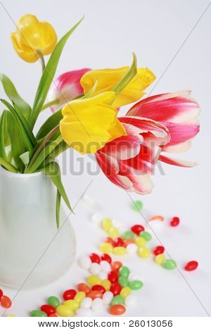 Home appliance - beautiful tulips in vase on the table with small Easter eggs