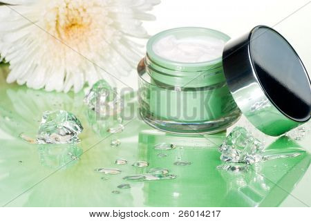 Closeup of container of moisturizing face cream and white chrysanthemum on green toned background with ice cubes