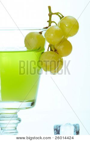 Glass of green colored liquor, bunch of grapes dipped into it with melted ice cubes around over white background with aqua colored gel