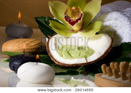 Avocado coconut scrub in coconut shell, orchid flower (Cymbidium sp.) and candles. Suited for relaxing and health commercials