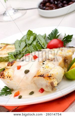 Grilled halibut with capers and pepper sauce served with grilled zucchini, lemon, lime, tomatoes. green peas and glass of white wine