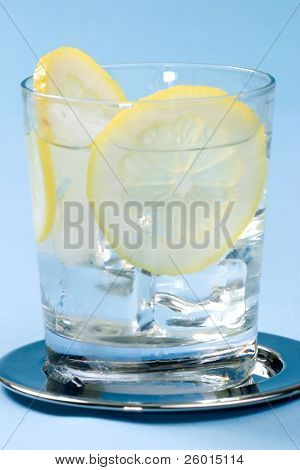 Closeup of chilled glasses of fresh water with sliced lemon and ice cubes over aqua paper background