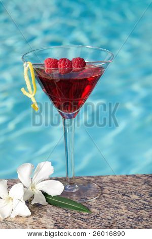 Glass of Raspberry Cosmopolitan cocktail on swimming pool side garnished with fresh raspberries