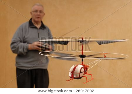 Senior man piloting tiny radio controlled helicopter indoors.  Shallow DOF with focus on helicopter.