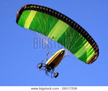 Paraglider against a solid blue sky.