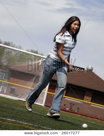 Young teen practicing lacrosse on her school field