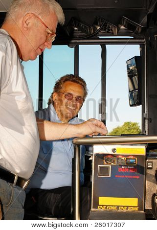Senior rider depositing his bus fare while the driver looks on.