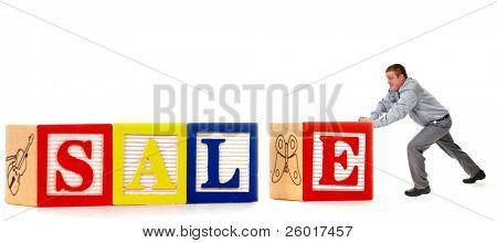 "Man pushing a big ""E"" to complete a SALE sign made of oversized alphabet blocks."