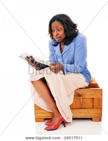Intense black woman reading her Bible.  Isolated on white.