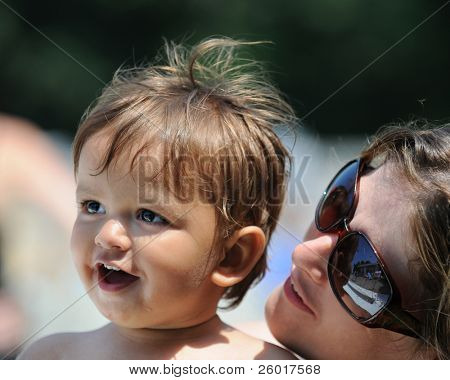 A close-up of a mom in sunglasses watching her smiling baby on a sunny day.