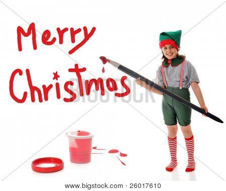 """Uma jovem garota vestida como duende do Papai Noel, pintura um sinal vermelho de """"Feliz Natal"""" com um artista de grandes dimensões"""