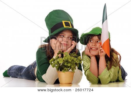 Two girls in green celebrating St. Patrick's Day with a gold pot of clover and an Irish flag.  Isolated on white.