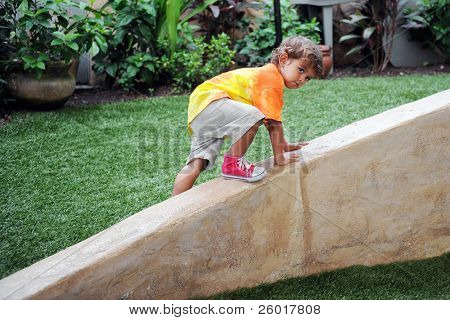A two-year-old cautiously climbing up a diagonal concrete wall.