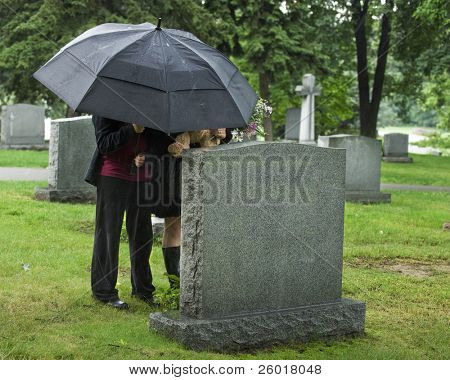 Two young people under an umbrella bringing a teddy bear and flowers to a grave site in the rain.