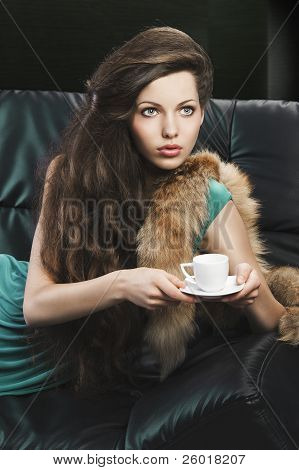 Young Elegant Girl In Green With Cup. She Is Looks At The Left