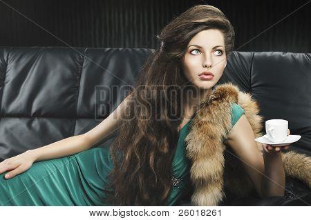 elegante junges Mädchen in grün mit Tasse. Sie nimmt den Pokal mit der linken hand