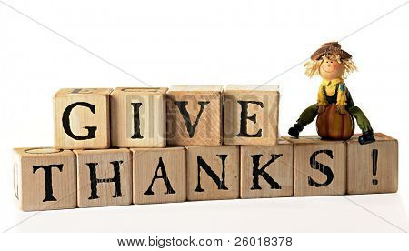 "Rustic alphabet blocks arranged to spell out, ""Give Thanks!""  A tiny scarecrow figurine with a pumpkin sits on top.  Isolated on white."