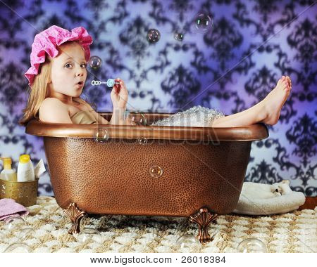 A beautiful preschooler blowing bubbles while wearing a bath bonnet in an old-time copper tub.