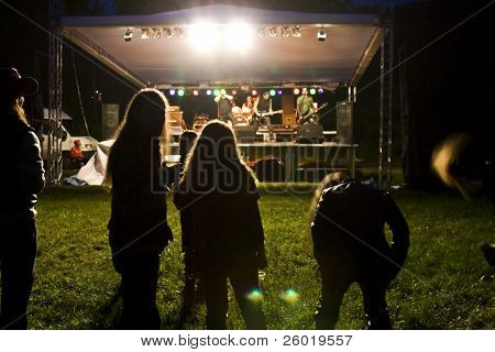 Young rockers with long hair having fun at a concert