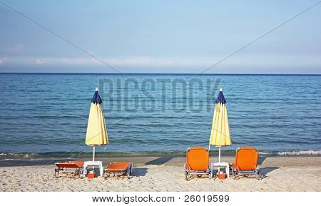 View of chairs and closed umbrellas on the beach at sunset