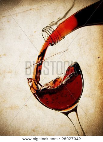 Red vine in glass on vintage background