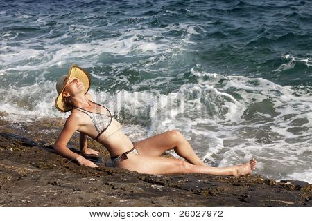 woman with hat sunbathing on rocks near big waves