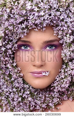Portrait of beautiful girl with stylish makeup and lilac around her face