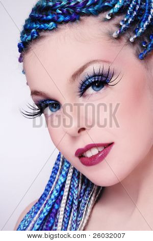 Close-up portrait of young beautiful girl with fancy blue hairstyle and extra long fake eyelashes