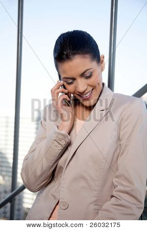 Pretty smiling female entrepreneur talking on cell phone