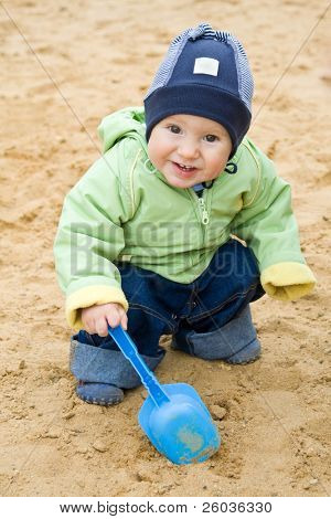 Child with a blue scoop in a sandbox