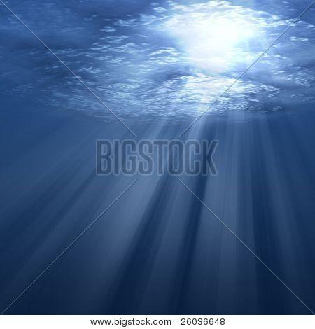Underwater scene with sun rays shining through water surface.
