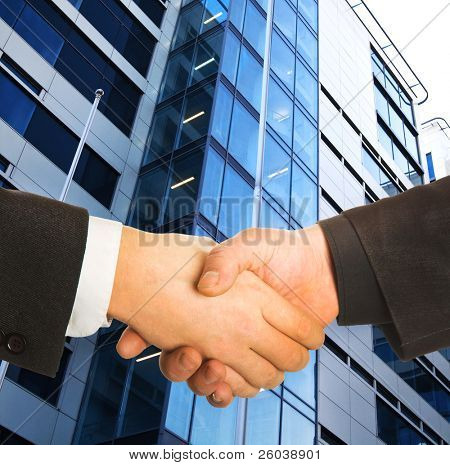 A business handshake in front of a building.