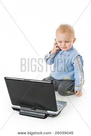 Concept of little businessman. Little child is speaking on the phone and working on laptop. Isolated on white background