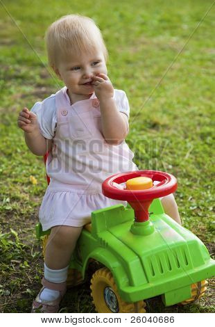 Little girl sitting on a green car